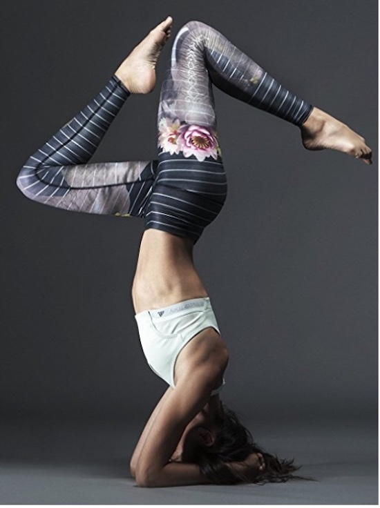 Woman wearing Teeki Hot Yoga Pants, she is in a forearm headstand with split legs.