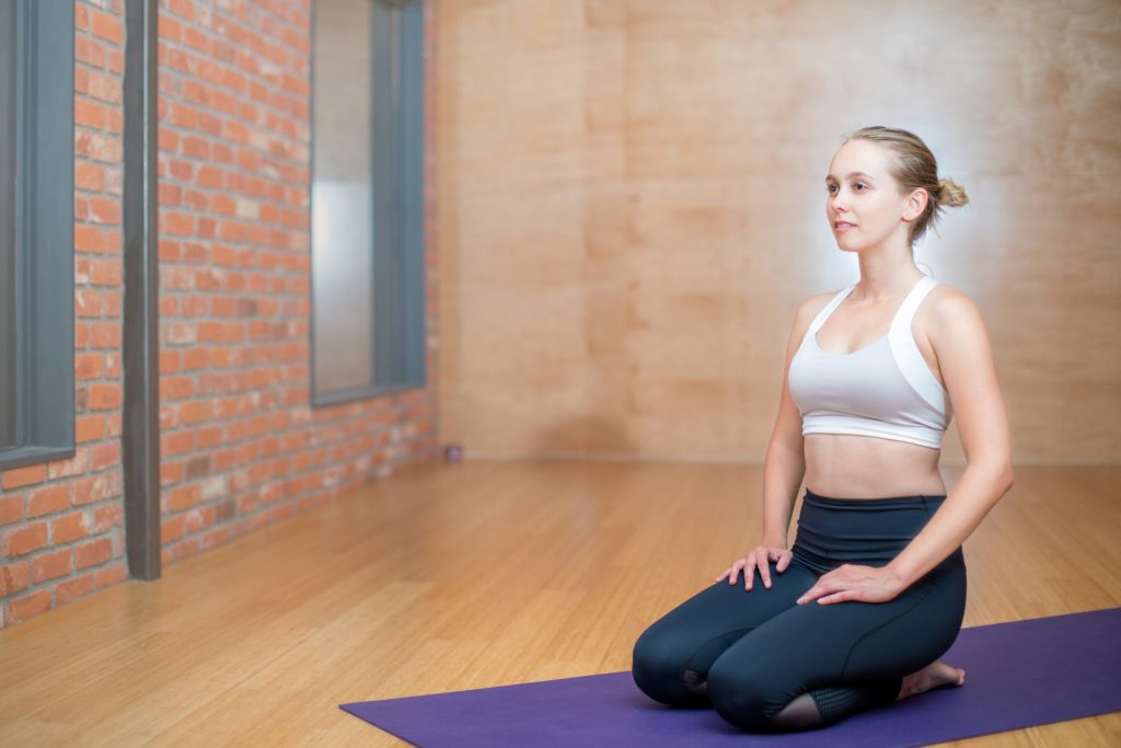 Woman on yoga mat wearing yoga pants and sports bra